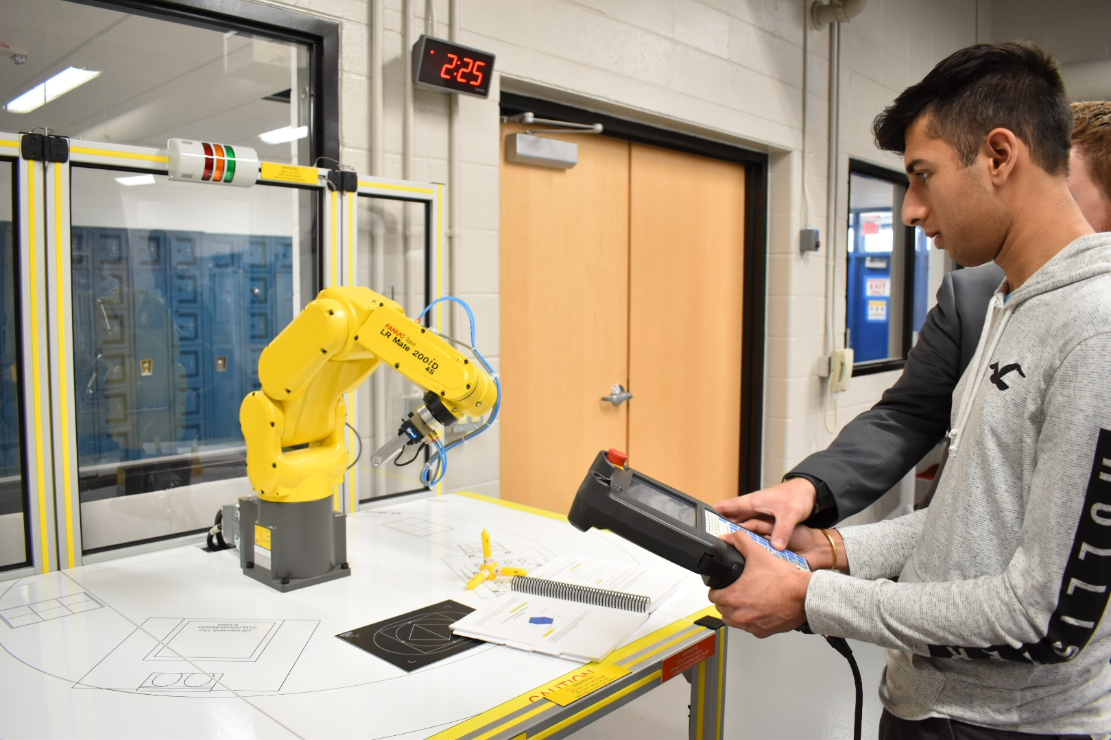 Germantown High School technology education student, guided by LAB Midwest's Mike Deitrich, operates a FANUC Fenceless CERT Cart Robot