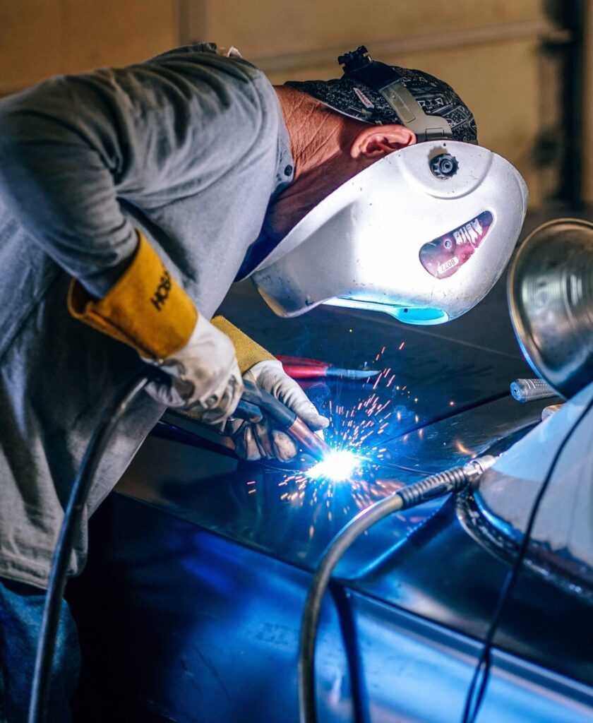 Man in manufacturing job welding a vehicle