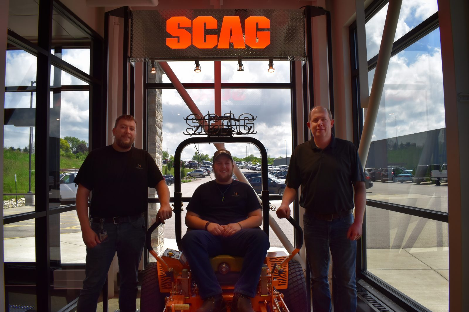 Metalcraft of Mayville employees, from left: Andy Pike, Kyle Pike, Kyle Gourlie, with the Scag mower that's painted using FANUC paint robots